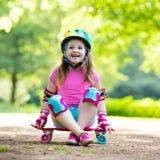 Planche à roulettes d'équitation d'enfant en parc d'été Photo libre de droits