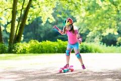 Planche à roulettes d'équitation d'enfant en parc d'été Photos stock