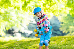 Planche à roulettes d'équitation d'enfant en parc d'été Images libres de droits