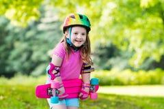 Planche à roulettes d'équitation d'enfant en parc d'été Photo stock