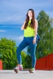 Planche à roulettes d'équitation de patineuse d'adolescente sur la rue Photos libres de droits