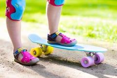 Planche à roulettes d'équitation d'enfant en parc d'été Photos libres de droits