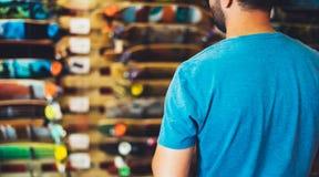 Planche à roulettes d'assortiment dans le magasin de magasin, personne choisissant et acheter des patins de couleur sur la fusée  photographie stock libre de droits