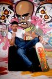 Planche à roulettes d'homme, mur de graffiti images libres de droits