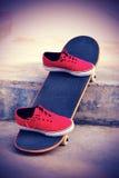 Planche à roulettes et espadrilles au skatepark Images stock