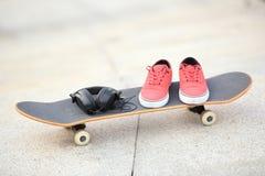Planche à roulettes et espadrilles au skatepark Photos stock