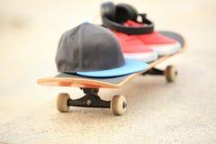 Planche à roulettes et espadrilles au skatepark Photographie stock