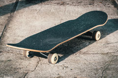 Planche à roulettes sur le plancher en béton dans le skatepark Photographie stock libre de droits