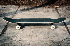Planche à roulettes sur le plancher en béton dans le skatepark Photos stock