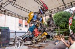Planche al músico gigante del robot, recogido de pedazos de metal grandes de la descarga, guitarra de los juegos, manejando su or Fotos de archivo libres de regalías