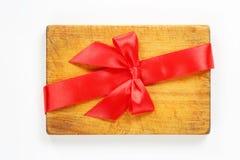 Planche à découper avec le ruban et l'arc rouges Photographie stock libre de droits