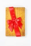 Planche à découper avec le ruban et l'arc rouges Photographie stock