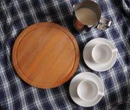 Planche à découper ronde, un broc de lait et tasses sur la nappe bleue de plaid avec l'endroit pour la conception Image stock