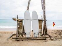 Planche de surf blanche abandonnée sur une plage sablonneuse vide avec des vagues dans la distance Images stock