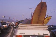 Planche de surf derrière le convertible, plage de coucher du soleil, Malibu, CA Images libres de droits