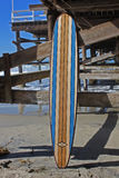 Planche de surf en bois contre le pilier de plage de la Californie Images libres de droits