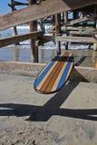Planche de surf en bois contre le pilier de plage de la Californie Photographie stock libre de droits