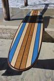 Planche de surf en bois contre le pilier de plage de la Californie Photos libres de droits