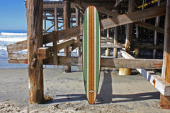 Planche de surf en bois contre le pilier de plage de la Californie Photos stock