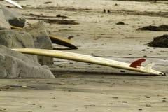 Planche de surf se penchant sur des roches à la plage Images stock