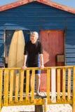 Planche de surf se tenante prêt d'homme supérieur à la hutte de plage Photo stock