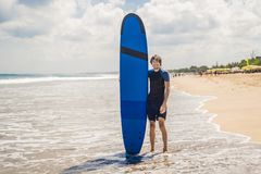 Planche de surf de transport d'homme au-dessus de sa tête Fermez-vous du type beau W photographie stock libre de droits