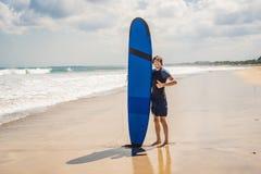 Planche de surf de transport d'homme au-dessus de sa tête Fermez-vous du type beau W photos stock