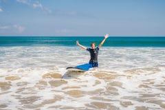 Planche de surf de transport d'homme au-dessus de sa tête Fermez-vous du type beau W image stock