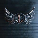Planche el ancla en un emblema con alas en un fondo del negro pintado Imagen de archivo