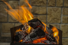 Planche el brasero con los carbones y la llama ardientes en fondo de la pared de piedra Imágenes de archivo libres de regalías