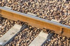 Planche el detalle ferroviario del tren oxidado sobre manera oscura del carril de las piedras Imagen de archivo libre de regalías