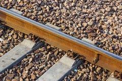 Planche el detalle ferroviario del tren oxidado sobre manera oscura del carril de las piedras Fotos de archivo libres de regalías