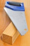 Planche en bois de coupe fraîche avec la scie de main Photographie stock libre de droits