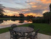 planche la tabla y la puesta del sol de patio en el agua Fotos de archivo