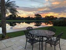 planche la tabla y la puesta del sol de patio en el agua Foto de archivo
