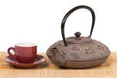 Planche la tetera con la taza roja de té en la estera de madera Imagen de archivo