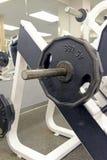Planche las placas del peso y el equipo del ejercicio en gimnasio Fotos de archivo