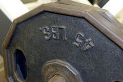 Planche las placas del peso y el equipo del ejercicio en gimnasio Fotos de archivo libres de regalías