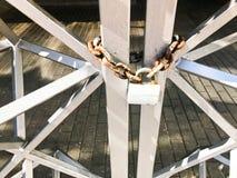 Planche las puertas, cerca de la barra de metal congelada en una cadena oxidada vieja fuerte de vínculos en una cerradura grande  imagenes de archivo