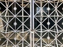 Planche las puertas, cerca de la barra de metal congelada en una cadena oxidada vieja fuerte de vínculos en una cerradura grande  imagen de archivo libre de regalías
