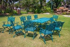 Planche las sillas verdes y la tabla al aire libre en el jardín imagen de archivo