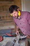 Planche masculine de coupe de charpentier par la scie circulaire image stock