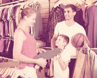 Planche à roulettes de achat d'homme et de femme pour le fils dans la boutique de sport Image libre de droits