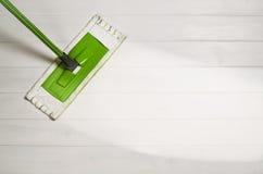 Plancher de nettoyage avec la vue supérieure de balai sur le fond en bois blanc image stock