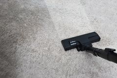 Plancher de nettoyage d'homme de service de nettoyage avec la machine sur le tapis à W photo stock