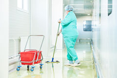 Plancher de nettoyage de travailleur avec le balai Images stock
