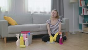 Plancher de nettoyage femelle de mouvement lent et compter sur le sofa dans le salon clips vidéos