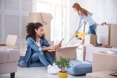 Plancher de nettoyage de jeune fille tandis que son compagnon de chambre regardant la photo Image libre de droits