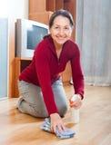 Plancher de parquet rubing de sourire de femme mûre Photographie stock libre de droits