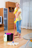 Plancher de sourire de nettoyage de fille Photo stock